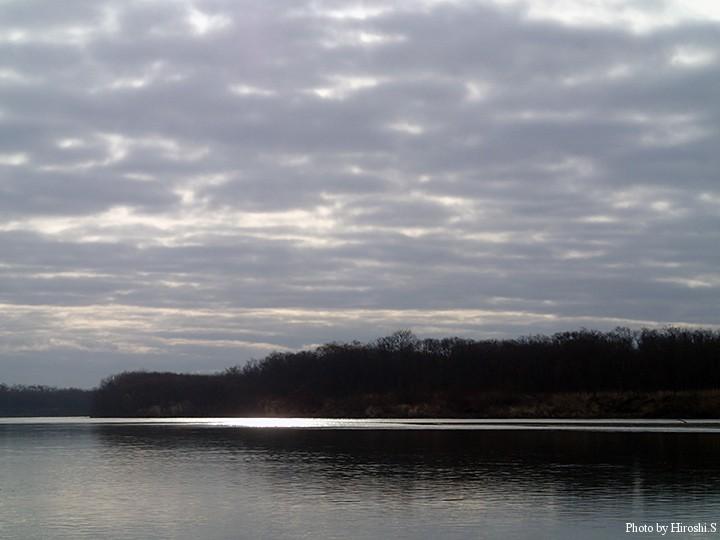 僅かに見える雲の合間から、一瞬だけ川を照らした。