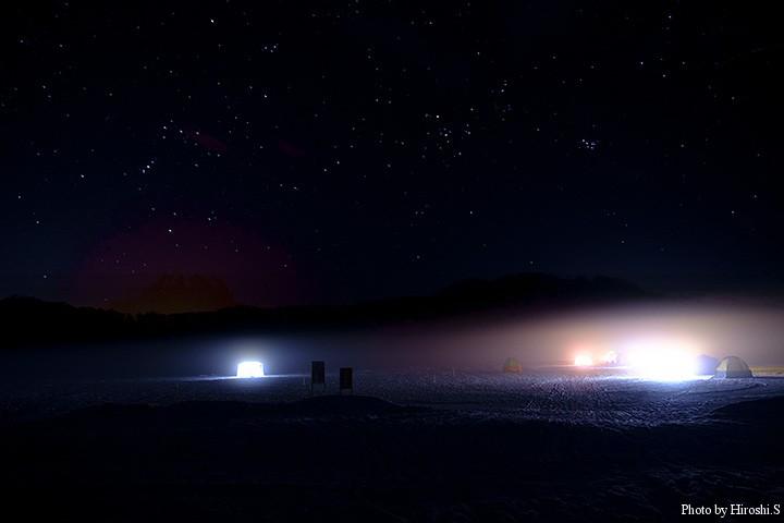深夜の網走湖 テントが並ぶ湖上にオリオン座が見える。